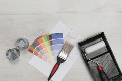 Paintbrush, Roller, Swatches, Cans of Paint, and Blueprints Over royalty free stock photography
