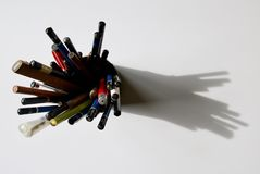 Overhead shot of a pencil container full of various different pencils casting a shadow stock photography