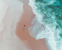 Overhead shot of people enjoying a sunny day at a sandy beach near beautiful waves of the sea stock image