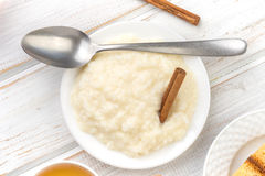 Overhead shot pile of rice pudding on porcelain plate, on wood Royalty Free Stock Image