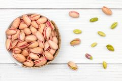 Overhead shot, roasted pistachios nuts in small bowl, some scattered on white boards desk stock images