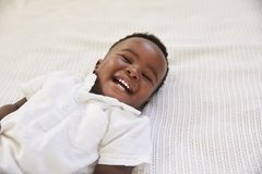 Overhead Shot Of Smiling Young Boy Lying On Bed Stock Photo