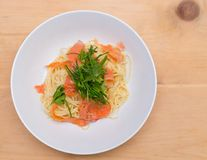 Overhead shot of a smoked salmon spaghetti with fresh herbs. stock photography