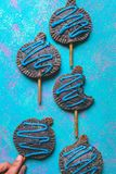 Overhead shot of tasty cookies on sticks with blue cream on them on a bright blue background royalty free stock photos