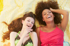 Overhead Shot Of Two Female Friends Lying On Bed Royalty Free Stock Image