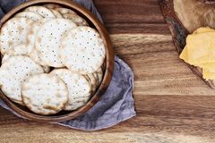 Overhead Shot of Water Crackers and Cheddar Cheese. Overhead shot of a bowl of water crackers and sliced cheddar cheese over a rustic background. Free copy space stock photography