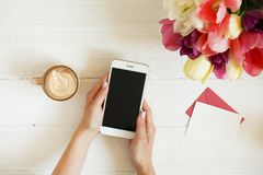 Overhead shot of woman hands holding cell phone gadget & coffee cup w cappuccino latte art on white wooden table background. Beaut Stock Photos