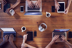 Overhead shot of young adults using technology at a table Royalty Free Stock Image