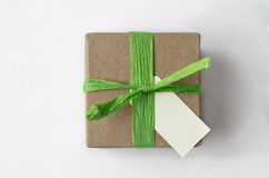 Overhead of Simple Brown Gift Box with Green Raffia Ribbon and B. Overhead shot of a simple brown gift box, with green raffia ribbon and blank label on white Stock Images