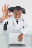 Overhead of a smiling doctor with laptop gesturing okay sign Stock Photos