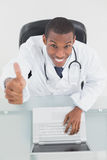 Overhead of smiling male doctor with laptop gesturing thumbs up Stock Image