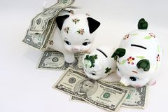 Overhead Spending. Three piggy banks representing a family with money all around Royalty Free Stock Image