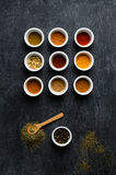 Overhead of Spice Bowls On Black Chalkboard with Scattered Herbs Royalty Free Stock Image