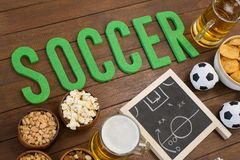 Strategy board, snacks and football on wooden table. Overhead of strategy board, snacks and football on wooden table Royalty Free Stock Photo