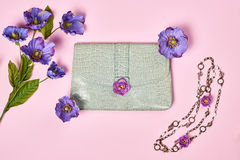 Overhead stylish Ladies essentials, flowers. Overhead outfit Fashion Ladies, accessories. Glamor creative  handbag clutch, flowers, necklace. Focus on Pastel Royalty Free Stock Photo