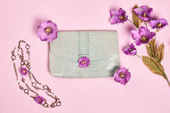 Overhead stylish Ladies essentials, flowers. Overhead outfit Fashion Ladies, accessories. Glamor creative  handbag clutch, flowers, necklace. Focus on Pastel Royalty Free Stock Photos