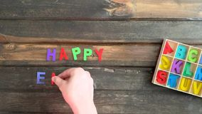 Overhead time lapse video of a child`s hand spelling out Happy Easter holiday message in colored block letters on a wooden stock footage
