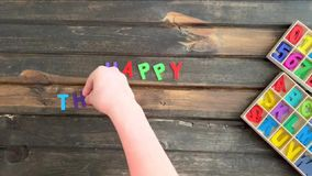Overhead time lapse video of a child`s hand spelling out Happy Thanksgiving message in colored block letters on a wooden stock footage