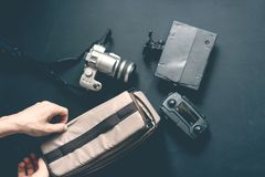 Overhead top view of hand put camera accessories in bag on dark background royalty free stock photo