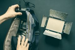 Overhead top view of hands put camera accessories in the bag on a dark surface royalty free stock photos