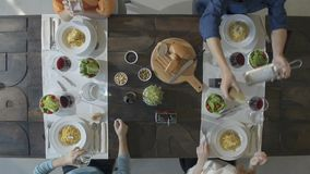 Overhead top view table four caucasian friends eating carbonara italian spaghetti pasta at lunch or dinner,drinking. Toasting together with red wine glasses stock footage