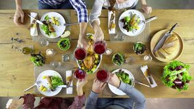 Overhead top view table four caucasian friends eating lunch, drinking, toast together with chicken,sala, potatoes, red stock video footage