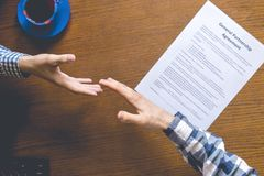 Overhead top view of two workers in casual in the office signing the contract agreement on table stock photography