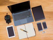 Overhead top view of wooden desk with computing gear Royalty Free Stock Photo