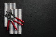 Various cutlery and folded napkin on concrete background. Overhead of various cutlery and folded napkin on concrete background Royalty Free Stock Photos