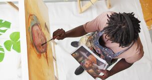 Overhead view of african american male artist painting on canvas looking at photo at art studio