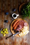 Overhead view of aperitif table Meat snack, fried sausages, cheese, salami, olives and a glass of wine on a dark table Menu and re. Staurant concept Flat lay royalty free stock photo