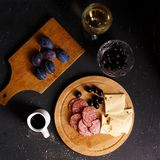 Overhead view of aperitif table Meat snack, fried sausages, cheese, salami, olives and a glass of wine on a dark table Menu and re. Staurant concept Flat lay royalty free stock images