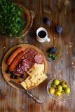 Overhead view of aperitif table Meat snack, fried sausages, cheese, salami, olives and a glass of wine on a dark table Menu and re royalty free stock images