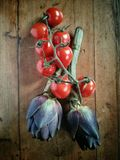 Overhead view of artichokes and tomatoes. Overhead view of two artichokes and some tomatoes on a wooden table Stock Photography