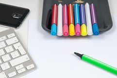 Overhead view of an artists desk with computer keyboard and pens Stock Image