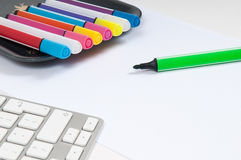 Overhead view of an artists desk with computer keyboard and pens Royalty Free Stock Images