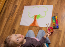 Little girl painting with watercolours. Overhead view of an attractive little girl kneeling on a hardwood floor painting a colourful tree on a sheet of paper Royalty Free Stock Photo