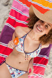 Overhead view of an attractive woman in bikini holding an orange ice lolly Royalty Free Stock Image