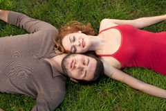 Young couple sleeping on green grass Royalty Free Stock Image