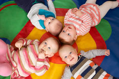 Overhead View Of Babies Lying On Mat At Playgroup Stock Images