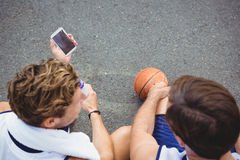 Overhead view of basketball player showing mobile phone to friend Royalty Free Stock Photo