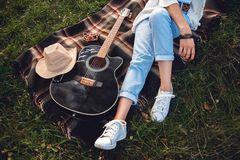 Overhead view of beautiful woman with guitar resting on green lawn. Top view stock photography