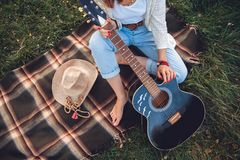 Overhead view of beautiful woman with guitar resting on green lawn. Top view stock photos