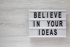 Overhead view, `Believe in your ideas` words on modern board over white wooden surface. Flat lay, from above, overhead. Copy spa royalty free stock photos