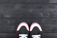 Overhead view of black and white shoes on black wooden floor. Shoes on a wooden background. Sneakers on a wooden floor. Sport Royalty Free Stock Photo