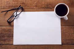 Blank paper with black coffee and spectacles on wooden table. Overhead view of blank paper with black coffee and spectacles on wooden table Royalty Free Stock Photography