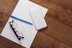Blank paper, mobile phone, pen and spectacles on wooden table. Overhead view of blank paper, mobile phone, pen and spectacles on wooden table Royalty Free Stock Photography