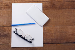 Blank paper, mobile phone, pen and spectacles on wooden table. Overhead view of blank paper, mobile phone, pen and spectacles on wooden table Stock Photography