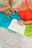 Overhead view of a blonde woman reading a book Stock Photos
