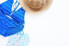 Overhead view of blue color swimwear with sandal and hat with copy space on white Stock Photography